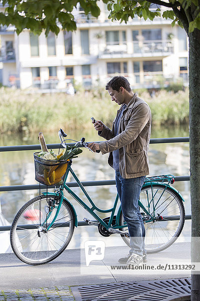 Young man standing by bicycle  using phone