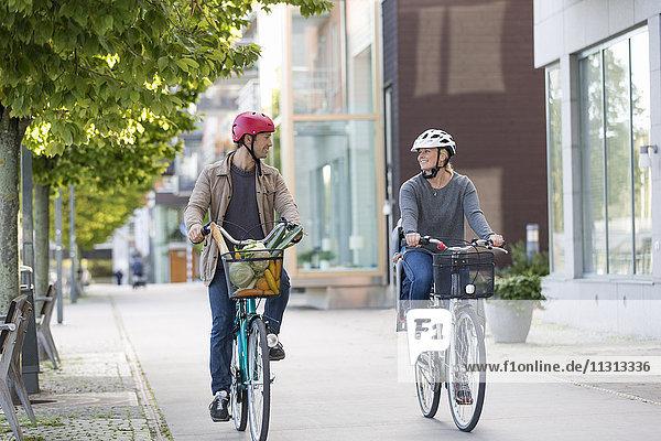 Couple cycling on sidewalk