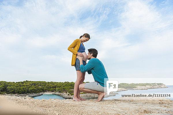 Mann küsst Bauch einer schwangeren Frau am Meer