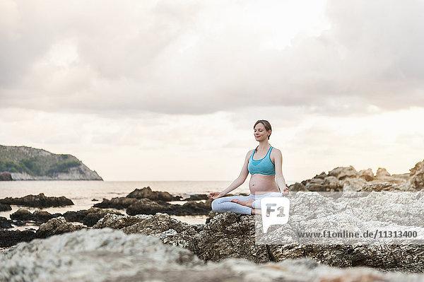 Schwangere Frau beim Yoga am Meer