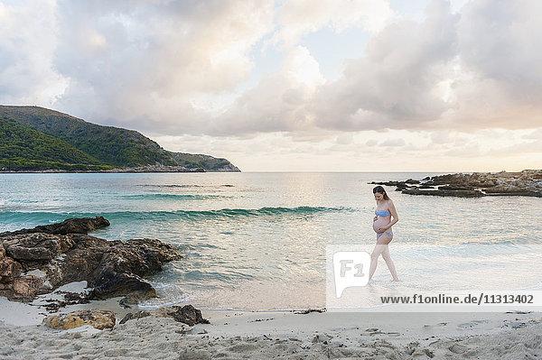 Eine schwangere Frau  die am Strand spazieren geht.