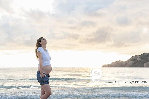 Glückliche schwangere Frau am Strand