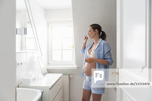 Schwangere Frau im Bad beim Zähneputzen
