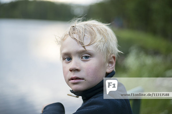 Portrait of young blond boy by lake