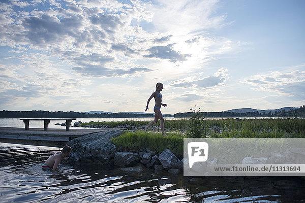 Boy and girl swimming in lake