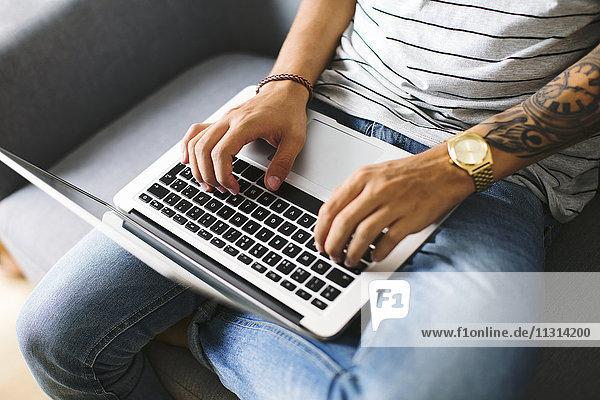 Teenager-Junge sitzt auf der Couch zu Hause mit Laptop  Teilansicht
