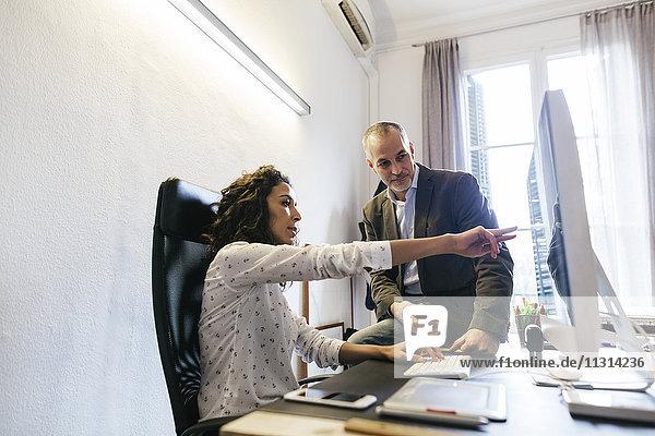 Geschäftsmann und Frau im Büro arbeiten gemeinsam am Computer