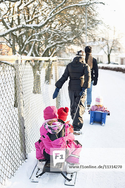 Rear view of parents pulling sleighs with sitting children