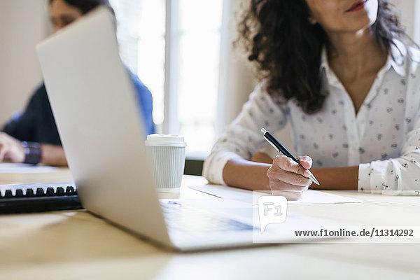 Geschäftsfrau sitzt im Meeting und macht sich Notizen mit einem Kugelschreiber.