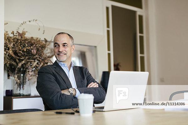 Erfolgreicher Geschäftsmann sitzt am Schreibtisch und arbeitet mit einem Laptop.
