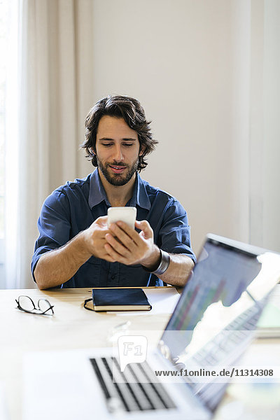 Geschäftsmann im Büro sitzend mit Smartphone