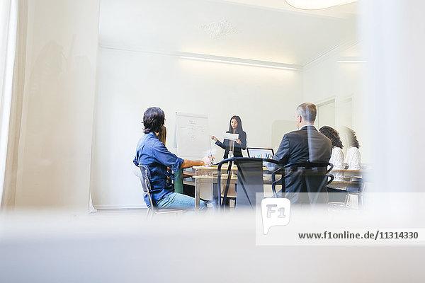 Geschäftsleute mit einer Teambesprechung hinter Glastüren