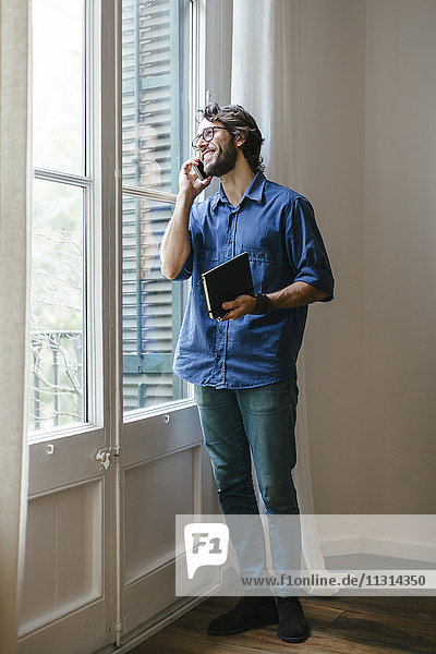 Businessman standing at office window  using smart phone