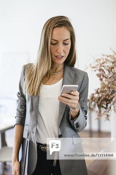Geschäftsfrau überprüft Nachrichten auf ihrem Smartphone  sieht besorgt aus.