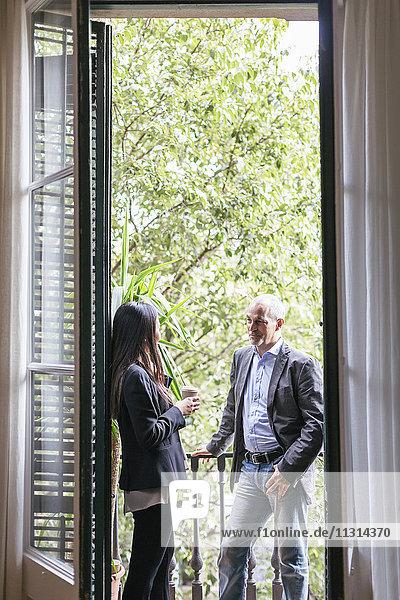 Geschäftsmann und Frau auf dem Balkon stehend  redend