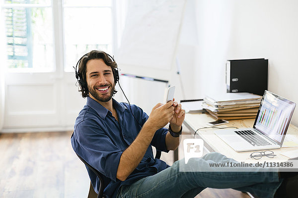 Geschäftsmann im Büro mit Kopfhörer und Smartphone  Füße hoch
