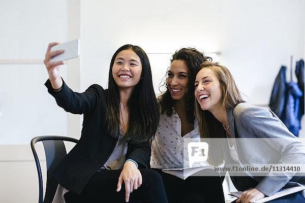 Drei Geschäftsfrauen  die sich mit einem Smartphone selbstständig machen