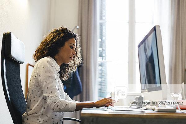 Erfolgreiche Geschäftsfrau im Büro bei der Arbeit am Computer