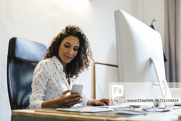 Erfolgreiche Geschäftsfrau sitzt im Büro und hält ein Smartphone.