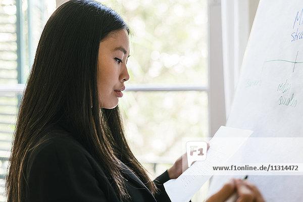 Junge Geschäftsfrau bei der Vorbereitung der Präsentation  Schreiben auf Flipchart