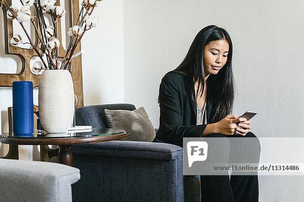 Geschäftsfrau sitzend in der Lounge mit Smartphone