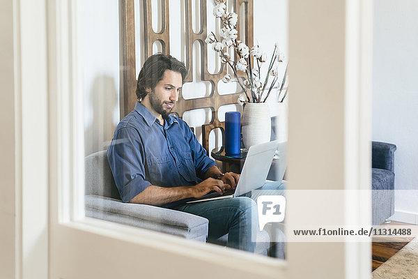 Geschäftsmann sitzend in der Bürolounge  mit Laptop