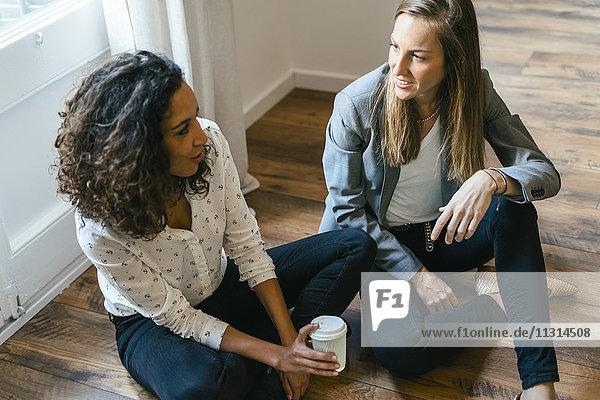 Zwei Collagen sitzen auf dem Boden  reden und frönen Kaffee