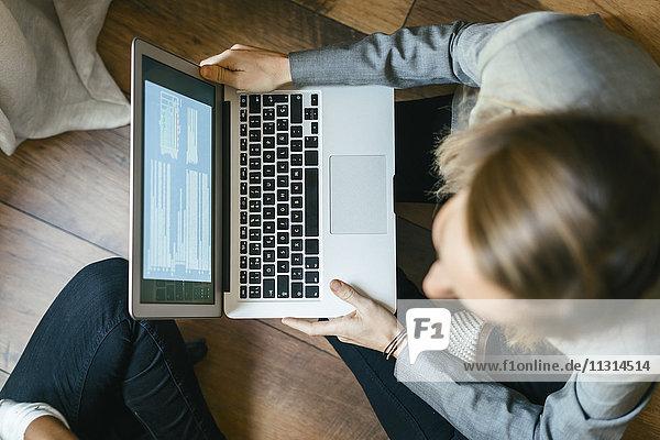 Geschäftsfrau auf dem Boden sitzend  mit Laptop auf dem Schoß arbeitend