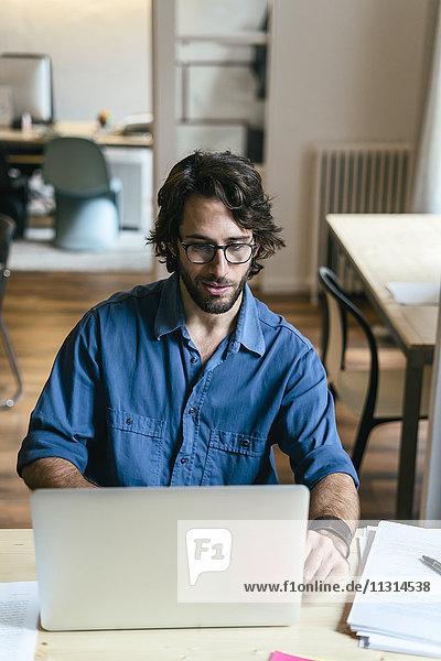 Geschäftsmann im Büro sitzend  am Laptop arbeitend