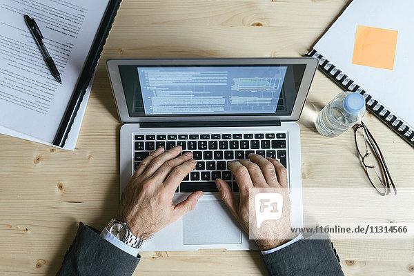 Geschäftsmann sitzt im Büro und tippt auf Laptop