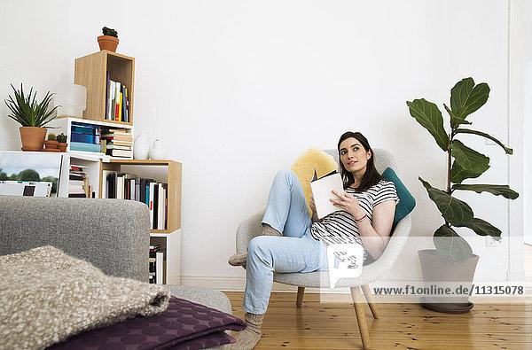 Frau zu Hause auf dem Stuhl sitzend  nach oben schauend