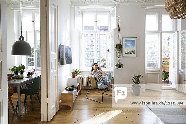 Frau zu Hause auf dem Stuhl sitzend spricht auf dem Handy