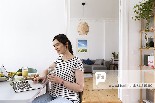Lächelnde Frau zu Hause am Tisch sitzend mit Laptop