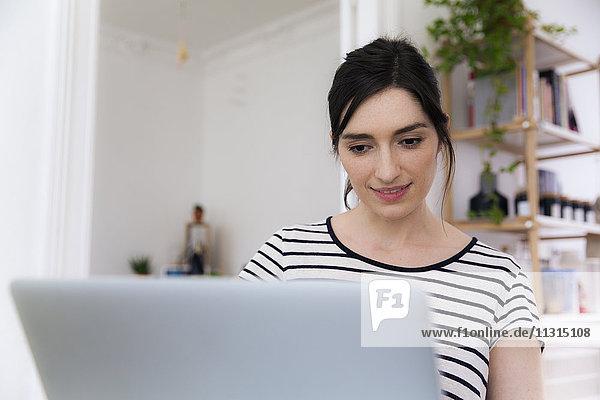 Lächelnde Frau zu Hause mit Laptop