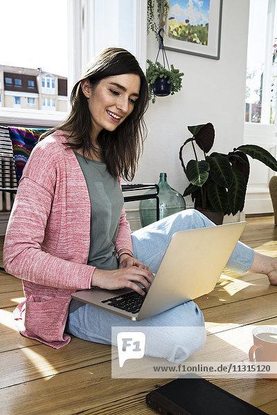 Frau zu Hause sitzend auf dem Boden mit Laptop