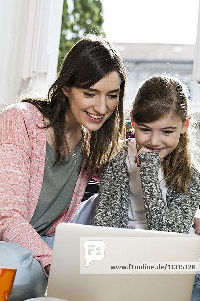 Lächelnde Mutter und Tochter mit Laptop