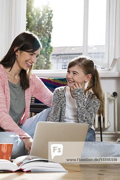 Glückliche Mutter und Tochter zu Hause auf dem Boden sitzend mit Laptop