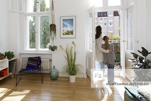 Mutter mit Tochter zu Hause an der Balkontür stehend