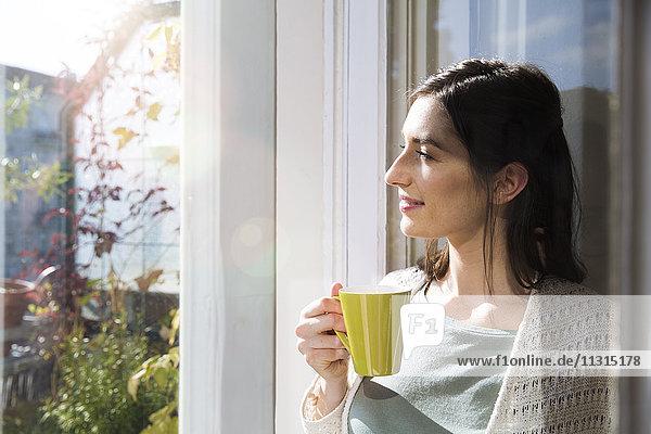 Lächelnde Frau mit einer Tasse Kaffee am Fenster
