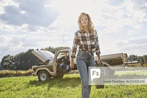 Frau geht mit Benzinkanister auf dem Feld neben dem Pick-Up Truck