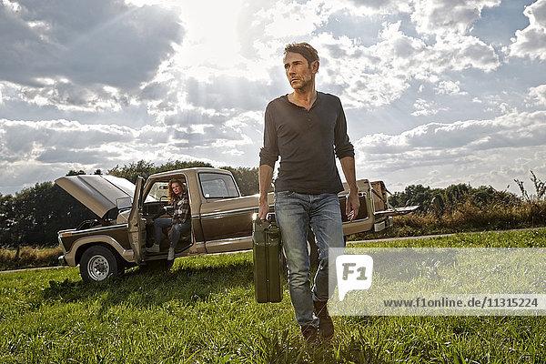 Mann  der mit Benzinkanistern auf dem Feld neben dem Pick-Up geht