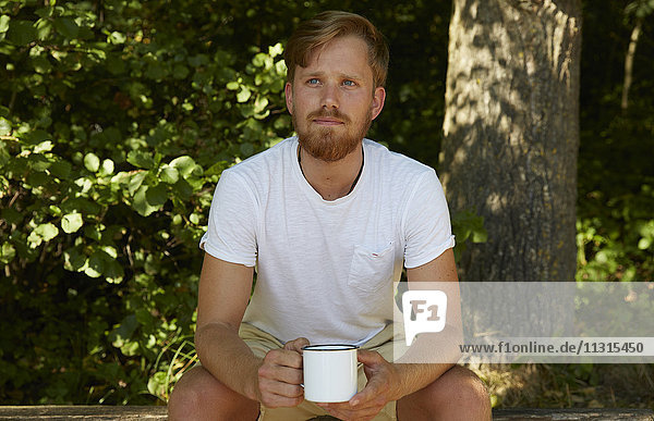 Young man holding a mug in nature