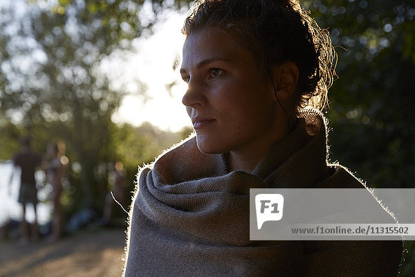 Young woman wrapped in a blanket at sunset
