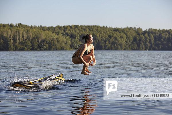 Frau springt vom Paddelbrett ins Wasser