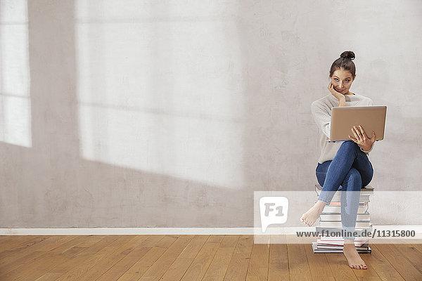Lächelnde junge Frau sitzt auf einem Bücherstapel mit Laptop