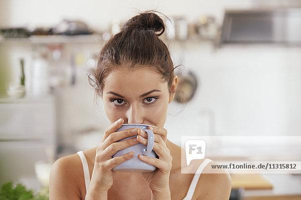 Junge Frau trinkt Kaffee in der Küche