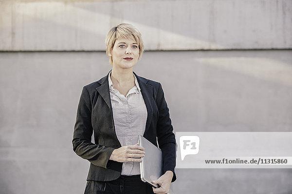 Portrait einer blonden Geschäftsfrau mit Laptop