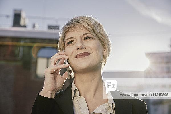 Porträt der lächelnden blonden Geschäftsfrau am Telefon bei Gegenlicht