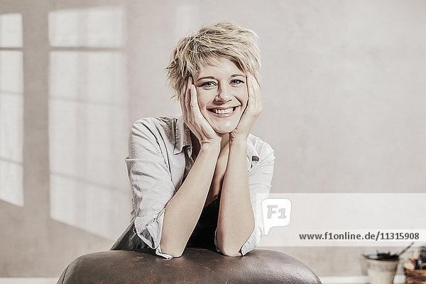 Porträt einer glücklichen blonden Frau mit Kopf in den Händen