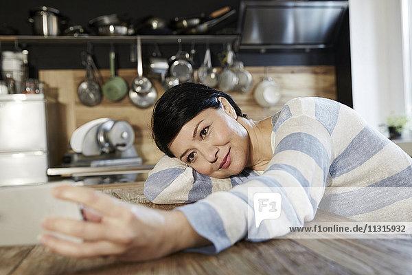Frau in der Küche ruht auf dem Tisch mit Handy